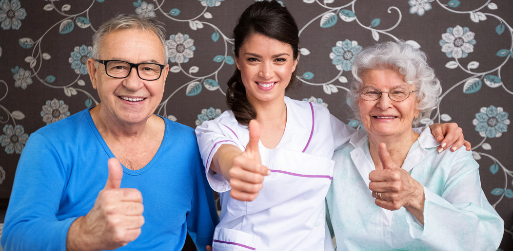 caregiver and elderly couple giving a thumbs up
