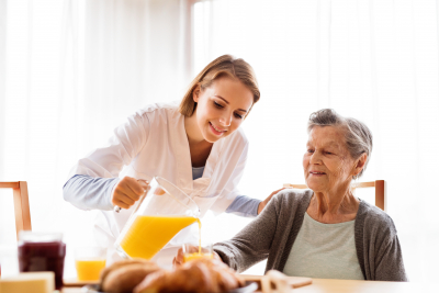 caregiver serving a glass of juice to the senior woman